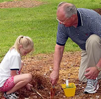 President, John Redding planting a tree with his grandaughter